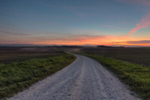Dusty country road towards the sunset