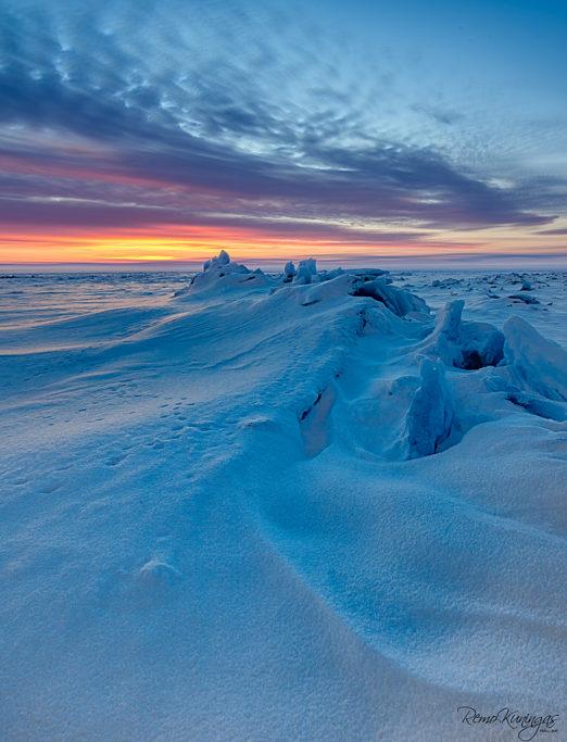 Lumega kaetud jäämurd laisalt looklemas tõusva päikese poole (Peipsi järv)